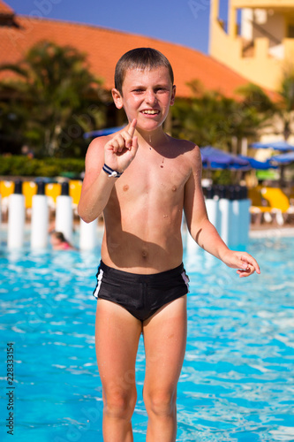 035a05e444 Slim kid coming out of swimming pool. Young boy on black swim wear ...