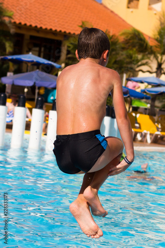 Young boy diving into swimming pool  Kid holding legs in the air