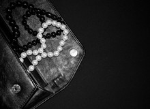 Jewelry In A Woman's Handbag. Beads Of Pearls And Amber On A Black Background. Black Clutch With Beads. A Lady's Purse.