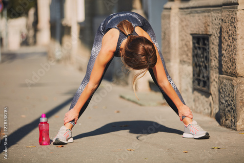 Fotografia  Portrait of  sporty young woman doing stretching in city.