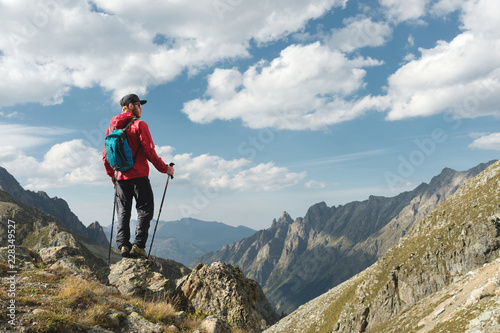Fotografiet A bearded man in sunglasses and a cap with a backpack stands on top of a rock and looks into a rocky valley high in the mountains