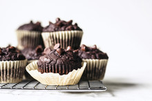 Chocolate Zucchini Muffins With Chocolate Chips On Cooling Rack