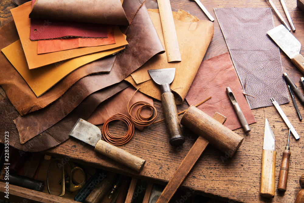 Fototapeta Leather craft or leather working. Selected pieces of beautifully colored or tanned leather on leather craftman's work desk .