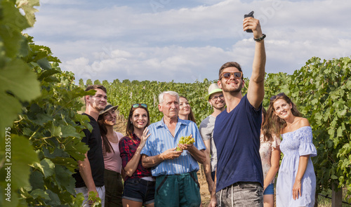 Photo  group of tourists take a selfie outdoor in the vineyard during a lesson about gr