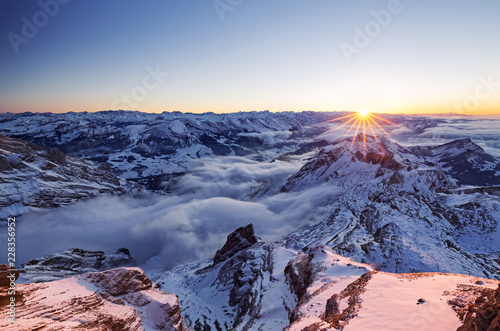 Aerial view of snow capped mountains during sunset
