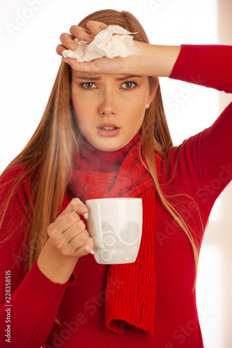 Fotografia  Young ill woman drinks tea as she has flu