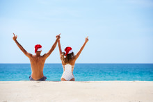 Happy Couple Sits White Beach In Christmas Hats