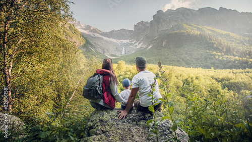 A young European family of three, mom, dad and two-year-old son sit on a rock and look at the mountain waterfall. the view from the back. Russia, Caucasus, Dombay