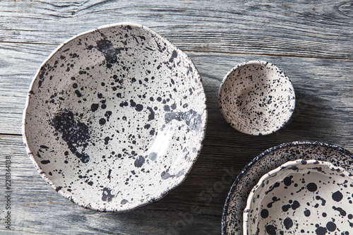 Foto Decorative pottery - bowls, plates covered with glazed on a gray wooden background