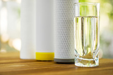 A Glass Of Purified Water And Filter Cartridges On Wooden Table On Green Natural Background