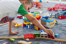 Little Child Playing With Wooden Railway On The Floor. Little Boy Playing With Wooden Train Set