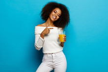 Beautiful Smiling African American Girl Showing A Glass Of Orange Juice