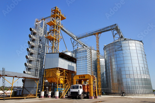 Agricultural silo truck of orange color on the territory of grain storage in sunny weather Tablou Canvas