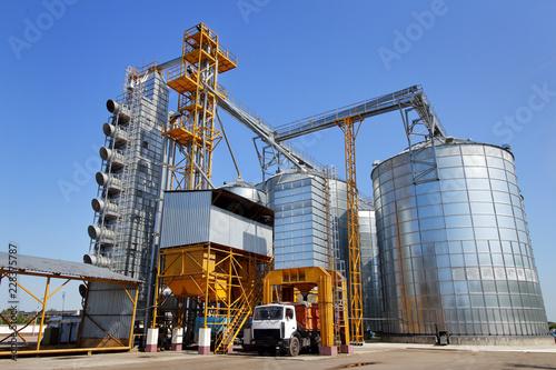 Fotografija  Agricultural silo truck of orange color on the territory of grain storage in sunny weather