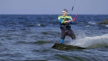 SLOW MOTION: A Male Kite Surfer Rolls On The Board On The Surface Of The Water.