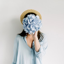 Young Woman Hold Blue Hydrangea Flower Bouquet On White Background. Flat Lay, Top View.