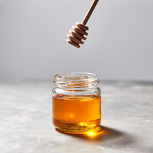 Natural Sunflower Honey In A Glass Pot And Dipper On A Gray Concrete Table. Jewish Rosh Hashanah Holiday.
