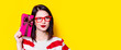 Leinwandbild Motiv Portrait of a young woman in glasses with gift box on yellow background