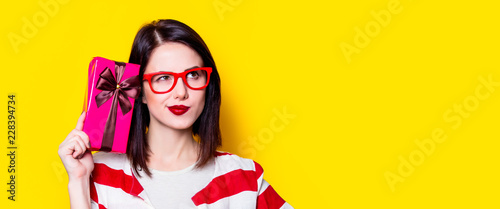 Portrait of a young woman in glasses with gift box on yellow background Poster Mural XXL