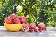 Fruta De La Granada En Una Mesa De Madera Y árboles En El Fondo