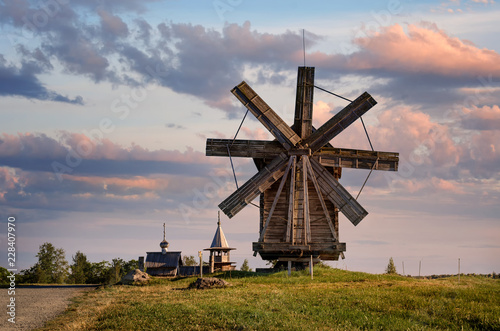 Kizhi Island, Russia, Karelia. A view of the wooden mill and the ancient religious architecture of the Kizhi Pogost. Summer landscape.