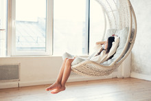 Young Teenage Girl Relaxing  In Comfortable Hanging Chair Near Window At Home. Child Sitting In Chair And Chilling Out. Relax Concept. Soft Colors, Warm Tone.