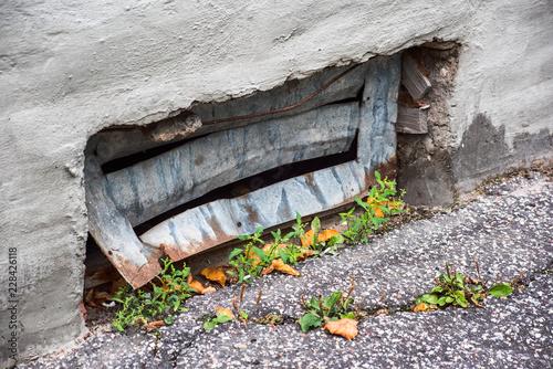 Fotografía  Bent basement grating and crack in asphalt
