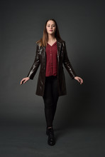 Full Length Portrait Of Brunette Girl Wearing Long Leather Coat And Boots. Standing Pose  On Grey Studio Background.