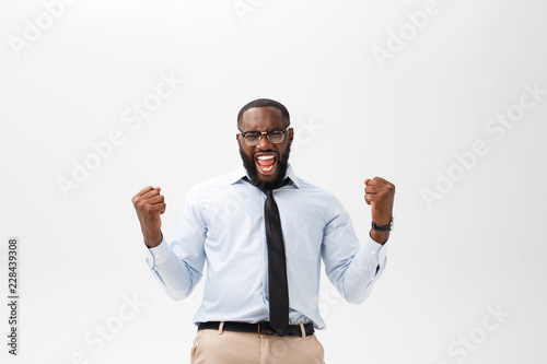 Deurstickers Ontspanning Happy african businessman wearing a corporate grey shirt and black tie punching the air with his fists arms in air, smiling and shouting in victorious success for his business deal