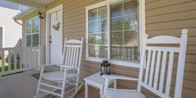 Home With Rocking Chairs And Table On Front Porch