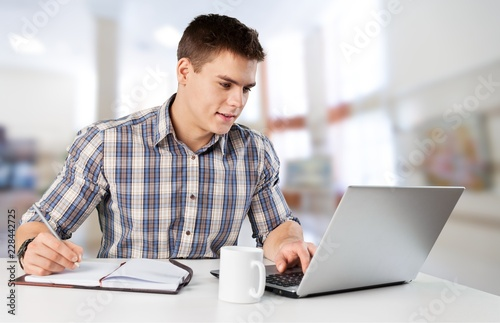 Happy young man works on his laptop