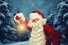 Santa Claus Holds A Lantern In His Hands And Looks Into The Camera Against The Background Of A Winter Forest.