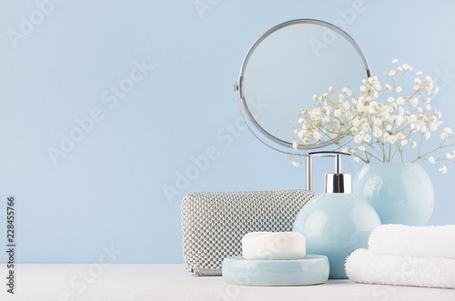 Fotografia Bathroom decor for female in light soft blue color - circle mirror, silver cosmrtic bag, white flowers, towel, soap and ceramic smooth vase on white wood table
