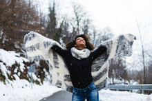 Blissful Black Woman Raising Arms Under The Snow In Winter At Mountain Road.