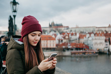 A Young Beautiful Tourist Girl Stands On The Charles Bridge In Prague In The Czech Republic And Uses A Mobile Phone To Call Or View A Map Or Mobile Application.