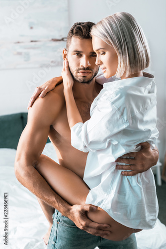 Fotografia  shirtless handsome man carrying his girlfriend in bedroom and looking at camera