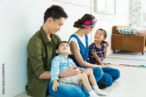 部屋の床に座る家族4人