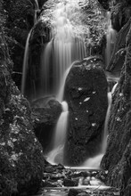 Beautiful Tall Waterfall Flowing Over Lush Green Landscape Foliage In Early Autumn In Black And White