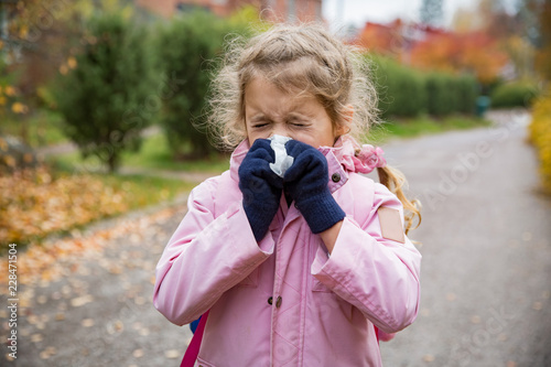 Valokuvatapetti Sick little girl with cold and flu standing outdoors