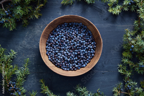 In de dag Aromatische Wooden bowl with seeds of juniper.