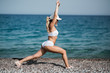 Beautiful woman is doing streching exercises on the beach