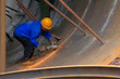 Workers are welding metal components in a steel plant