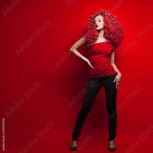 Fotografia Portrait of beautiful young woman with red hair on red background