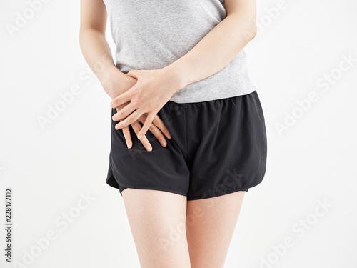 白背景で痛む股関節を押さえる女性 Wallpaper Mural