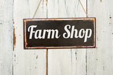 Old Metal Sign In Front Of A White Wooden Wall - Farm Shop