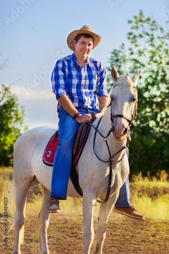 Photo The man in a shirt and a hat goes astride a horse