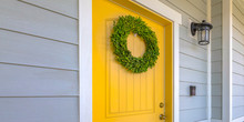 Wreath On Yellow Front Door And A Lamp On A Wall