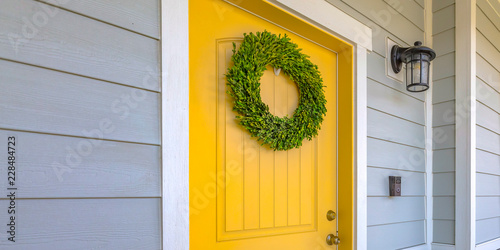 Wreath on yellow front door and a lamp on a wall Canvas Print