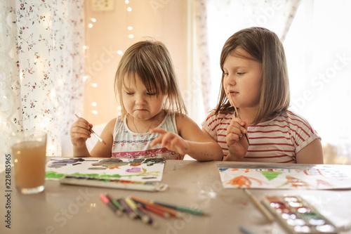 Fotografía  Sisters draw at table at home in real interior