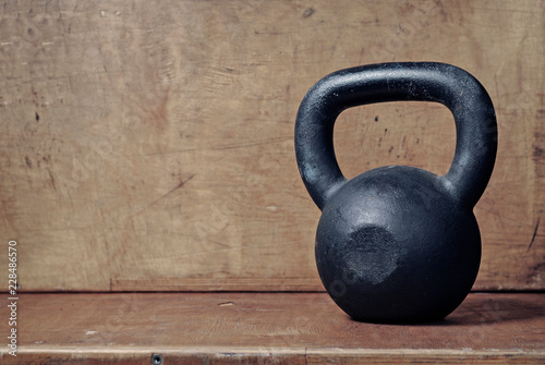 Heavy kettlebell in black on wooden background